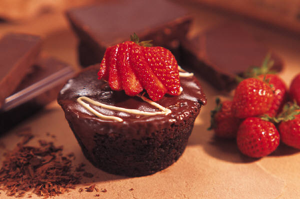 cupcake topped with chocolate ganache and strawberries